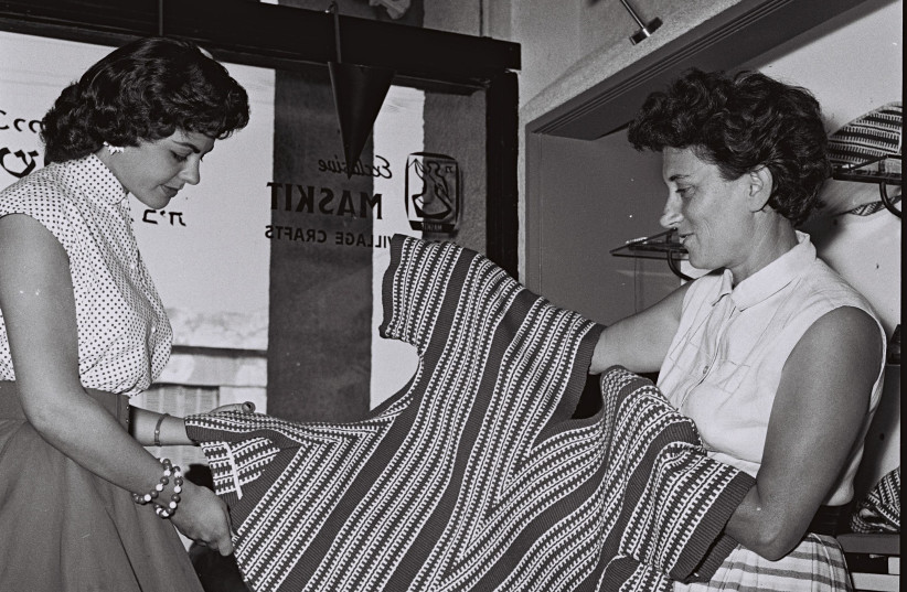 Ruth Dayan shows a handmade blouse to Israeli beauty queen Sarah Tal at Maskit's store on Tel Aviv's Ben Yehuda Street in 1956. (photo credit: HANS PINN/GPO)