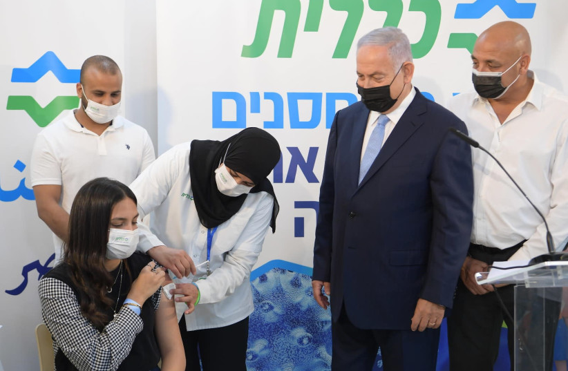 Prime Minister Benjamin Netanyahu visits Clalit vaccination center in the Arab town of Zarzir with Health Minister Yuli Edelstein to help encourage vaccination among the Arab population. (photo credit: AMOS BEN GERSHOM, GPO)