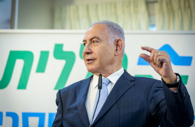 Prime Minister Benjamin Netanyahu is seen gesturing at a Clalit vaccination center in Zarzir, on February 9, 2021. (photo credit: DAVID COHEN/FLASH 90)