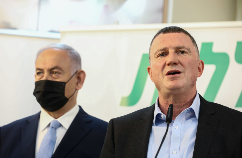 Health Minister Yuli Edelstein and Prime Minister Benjamin Netanyahu are seen speaking at a Clalit vaccination center in Zarzir, on February 9, 2021. (photo credit: DAVID COHEN/FLASH 90)