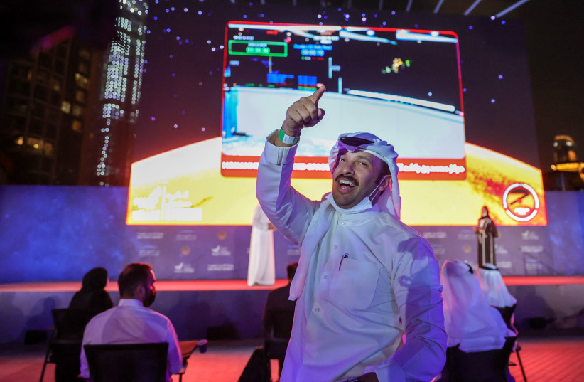 A man gestures as people watch a screen displaying information of the Hope Probe entering the orbit of Mars, in Dubai, United Arab Emirates, February 9, 2021. (photo credit: CHRISTOPHER PIKE/REUTERS)