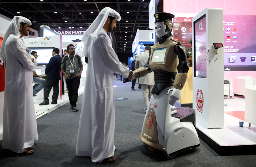Visitor shakes hands with an operational robot policeman at GISEC in Dubai (photo credit: REUTERS/STRINGER)