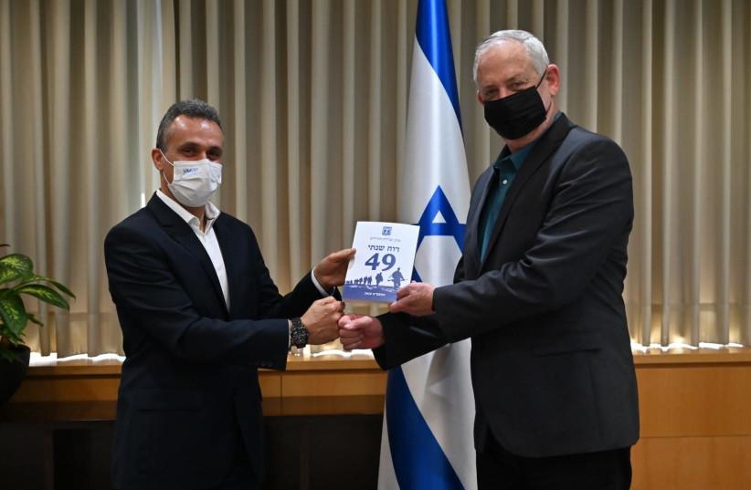 Defense Minister Benny Gantz and  Brig-Gen. (ret.) Eitan Dahan hold the report (photo credit: ARIEL HERMONI / DEFENSE MINISTRY)