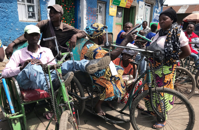 Disabled couriers sits on their tricycles as they wait to transport grocery at the no-man's-land amid the coronavirus disease (COVID-19) outbreak between Rwanda and Congo in Goma, Democratic Republic of Congo November 20, 2020 (photo credit: REUTERS/DJAFFAR AL-KATANY)