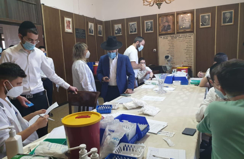 A vaccination drive by the Health Ministry for yeshiva students gets going in the Ponovizeh Yeshiva in Bnei Brak on Thursday afternoon. (photo credit: LEMAANCHEM)