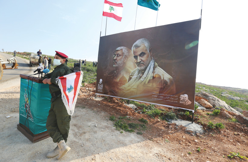 A HEZBOLLAH member holds a Lebanese flag in front of a picture depicting Iranian Gen. Qasem Soleimani and Iraqi militia commander Abu Mahdi al-Muhandis, in Khiam, Lebanon, last month. (photo credit: AZIZ TAHER/REUTERS)