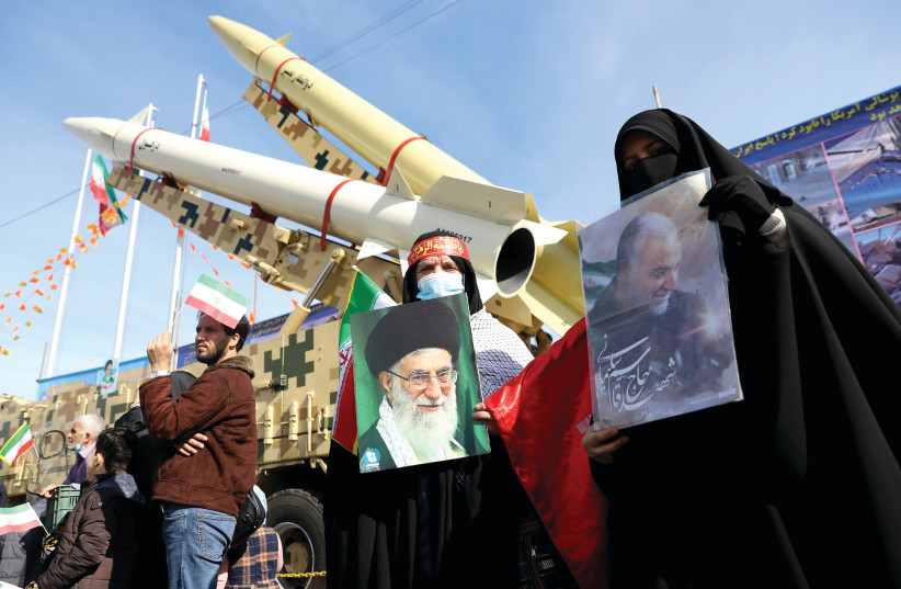 IRANIAN WOMEN hold pictures of Supreme Leader Ayatollah Ali Khamenei and the late Iranian Lt.-Gen. Qasem Soleimani, during the celebration of the 42nd anniversary of the Islamic Revolution, in Tehran on Wednesday. (photo credit: MAJID ASGARIPOUR/WANA (WEST ASIA NEWS AGENCY) VIA REUTERS)