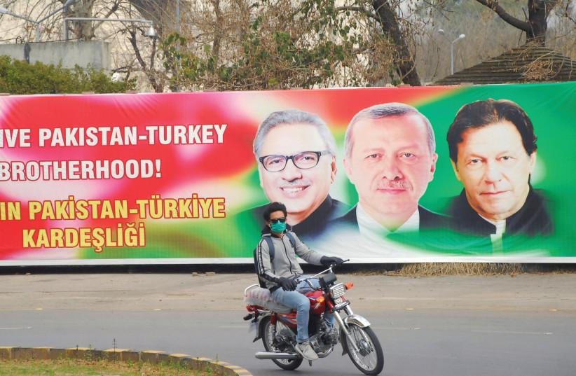 A MAN RIDES his motorbike past a sign showing Pakistan's President Alvi, Turkey's President Erdogan and Pakistan's Prime Minister Khan, in Islamabad, Pakistan, last year. (photo credit: WASEEM KHAN/REUTERS)