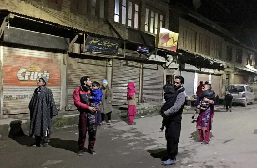 Residents carrying their children stand on a road after vacating their houses following an earthquake in Srinagar February 12, 2021.  (photo credit: REUTERS/STRINGER)