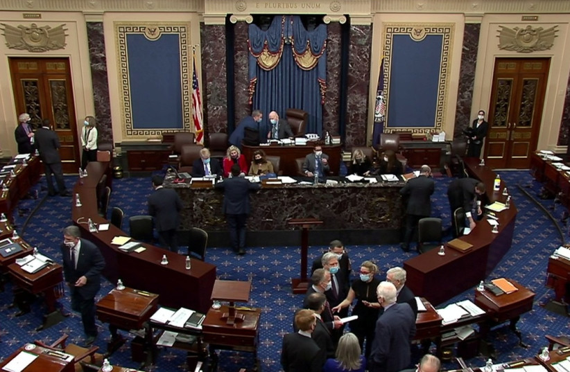 US Senate Minority Leader Mitch McConnell (R-KY) huddles on the Senate floor with Senator Kyrsten Sinema (D-AZ), Senator John Barrasso (R-WY), Senator John Hoeven (R-ND), Senator Dan Sullivan (R-AK), Senator James Lankford (R-OK), Senator Joni Ernst (R-IA) and Senator John Cornyn (R-TX) and others (photo credit: REUTERS)