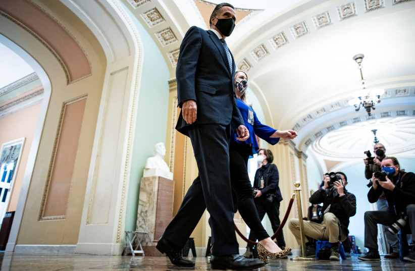 US Senator Mitt Romney (R-UT) walks to the Senate floor on the fifth day of the impeachment trial of former US president Donald Trump, on charges of inciting the deadly attack on the U.S. Capitol, in Washington, US, February 13, 2021 (photo credit: AL DRAGO/REUTERS)
