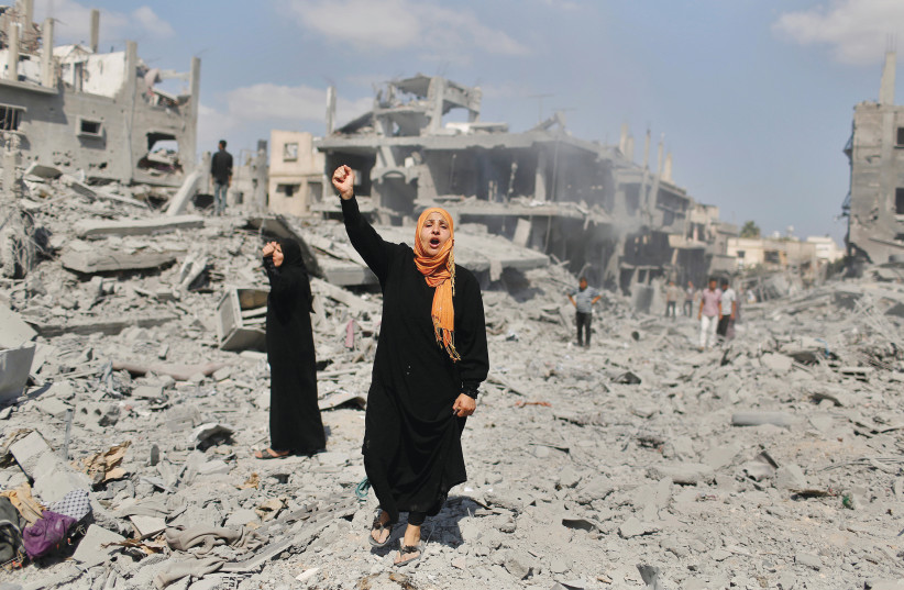 A WOMAN YELLS as she stands near her destroyed house in Beit Hanun, in the northern Gaza Strip in 2014. (photo credit: SUHAIB SALEM / REUTERS)