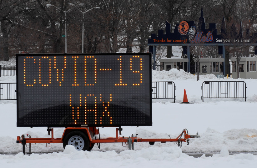 A sign saying 'COVID-19 VAX' is seen outside Citi Field, the home stadium of the MLB's New York Mets, one day ahead of the opening of a portion of the baseball park as a COVID-19 mass vaccination site in Queens, New York (photo credit: BRENDAN MCDERMID/REUTERS)