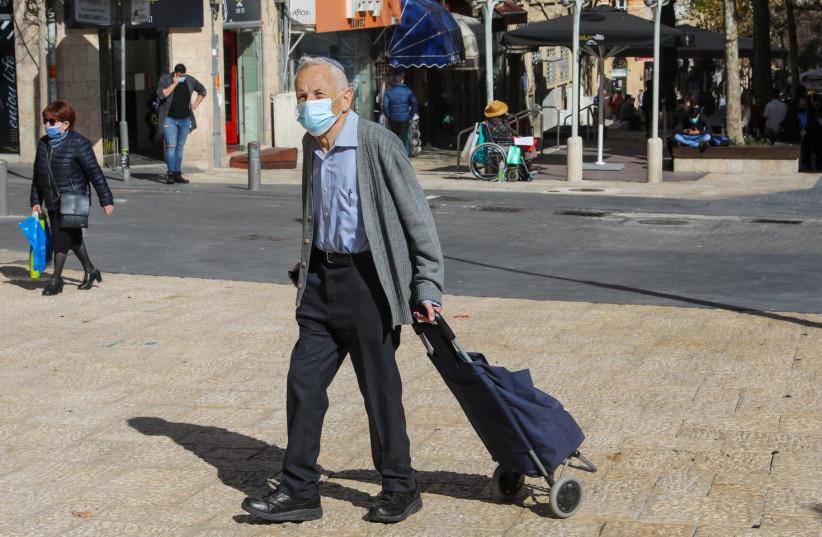 An elderly man walking in Jerusalem wearing a COVID-19 mask  (photo credit: MARC ISRAEL SELLEM)