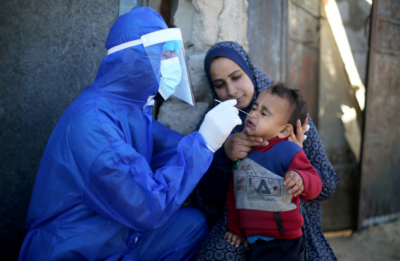 Palestinian medical worker collects a swab sample from a boy to be tested for the coronavirus disease (COVID-19), in the southern Gaza Strip January 14, 2021. (photo credit: REUTERS)