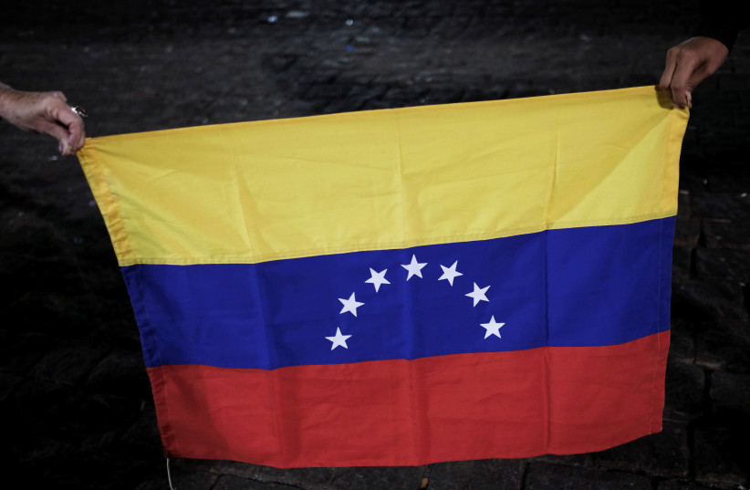 Venezuelans hold a Venezuelan flag as they take part in a protest in support of Venezuelan opposition leader Juan Guaido in Sao Paulo, Brazil, April 30, 2019. (photo credit: REUTERS/NACHO DOCE)