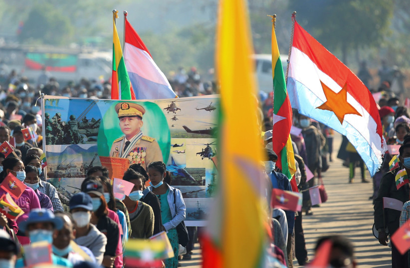 Military supporters carry a portrait of junta leader General Min Aung Hlaing as they celebrate the coup in Naypyitaw, Myanmar February 4, 2021 (photo credit: REUTERS/STRINGER)
