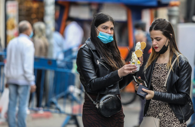 Israelis in Jerusalem are seen with ice cream ahead of an expected snowfall, on February 16, 2021. (photo credit: MARC ISRAEL SELLEM/THE JERUSALEM POST)