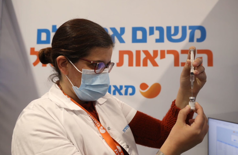 A medical worker is seen filling up a coronavirus vaccine dose at a Meuhedet vaccination center in Jerusalem, on February 16, 2021. (photo credit: MARC ISRAEL SELLEM/THE JERUSALEM POST)