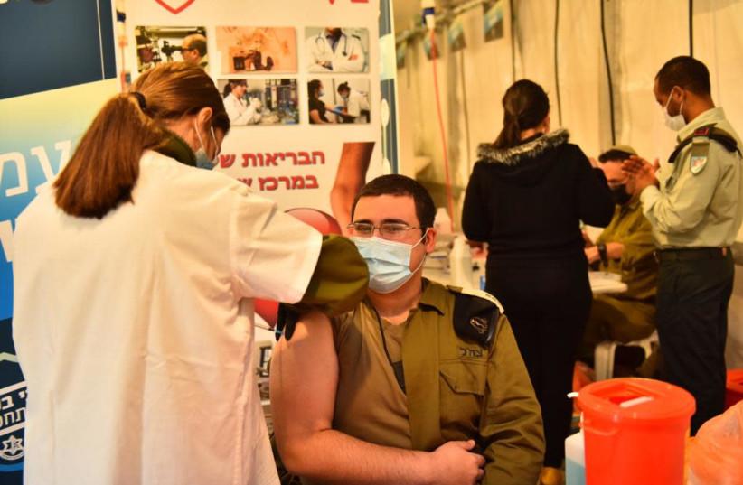 An IDF soldier is seen getting the coronavirus vaccine. (photo credit: IDF SPOKESPERSON'S UNIT)