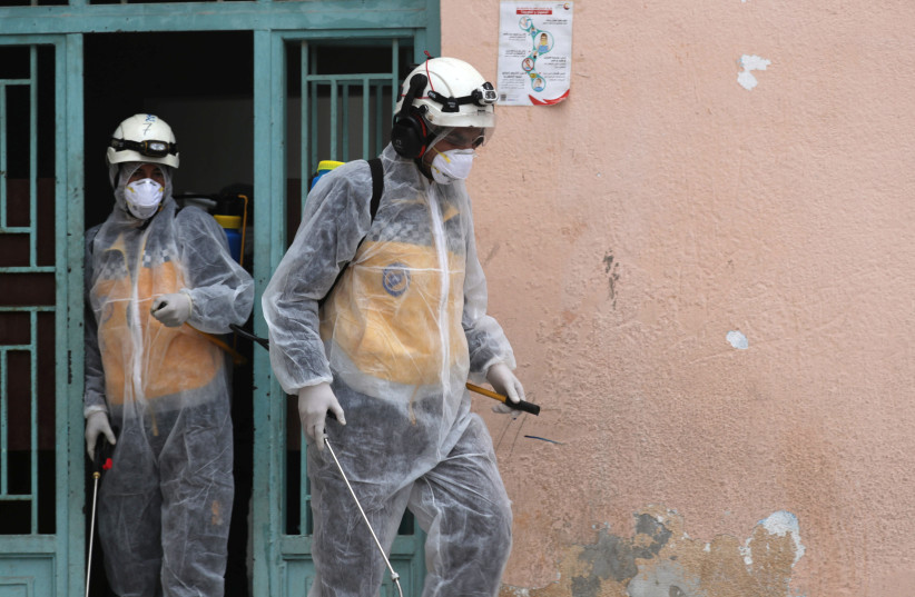 Members of the Syrian Civil defense wear protective gears as they sanitize a school as part of the preventive measures against the spread of the coronavirus, in Afrin, Syria March 18, 2020 (photo credit: REUTERS/KHALIL ASHAWI)