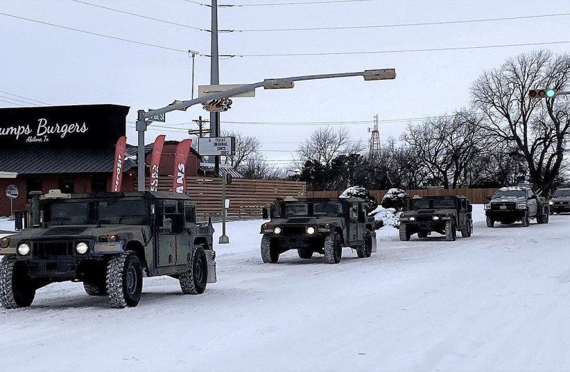 Military vehicles from the Texas Military Department of the Texas National Guard, tasked to transport residents to designated warming centers and other required duties, form a convoy in Abilene, Texas, U.S. February 16, 2021.  (photo credit: GREG JAKLEWICZ/REPORTER-NEWS/USA TODAY NETWORK VIA REUTERS)