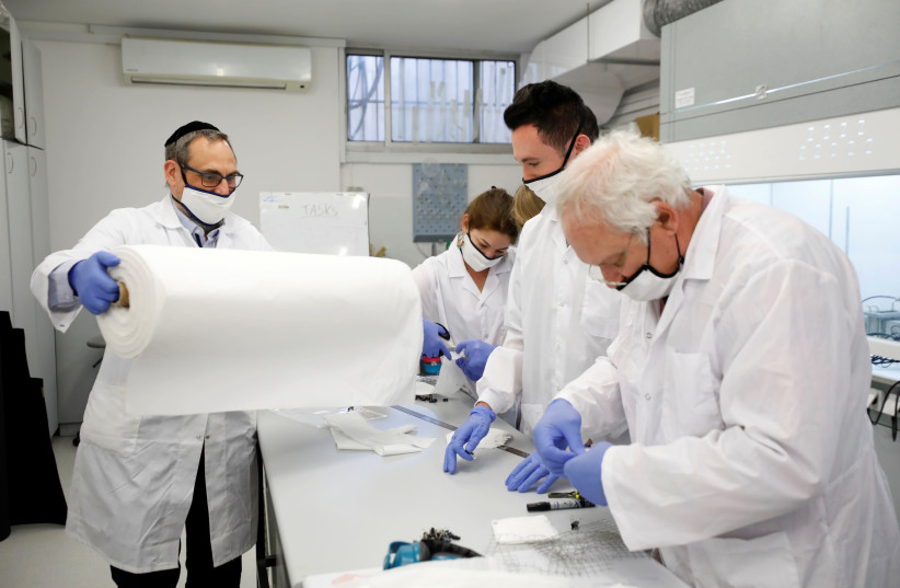 Employees of Israel's Sonovia Ltd, makers of washable and reusable antiviral masks, which the company says can help stop the spread of the coronavirus disease (COVID-19), work at their laboratory in Ramat Gan, Israel May 17, 2020.  (photo credit: AMIR COHEN/REUTERS)