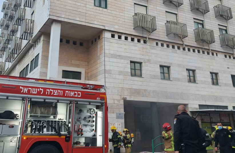 Firefighters work to put out a fire and evacuate residents from a nursing home on Gordon street in Hadera. (photo credit: FIRE AND RESCUE SERVICE)