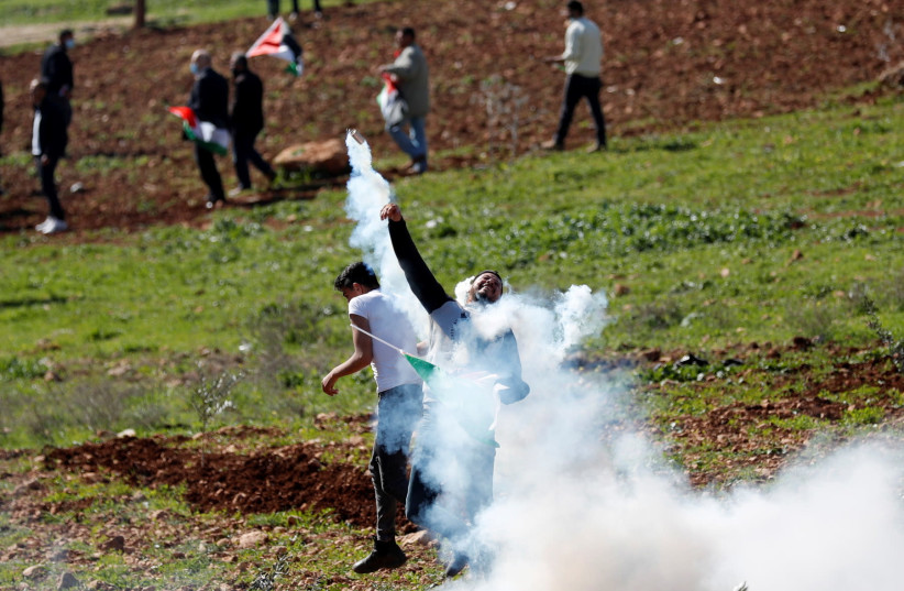 A Palestinian demonstrator returns a tear gas canister fired by Israeli troops during a protest against Israeli settlements, In Beit Dajan in the West Bank February 12, 2021. (photo credit: MOHAMAD TOROKMAN/REUTERS)