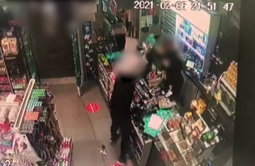 Security footage from the incident shows the suspect raging at the scene, throwing products around the store wildly as his spouse tries to hide in the corner behind a coworker. (photo credit: POLICE SPOKESPERSON'S UNIT)