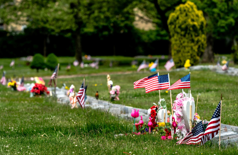 American flags sit on graves during Memorial Day following the outbreak of the coronavirus disease (COVID-19) in the Staten Island borough of New York US, May 25, 2020 (photo credit: JEENAH MOON/REUTERS)