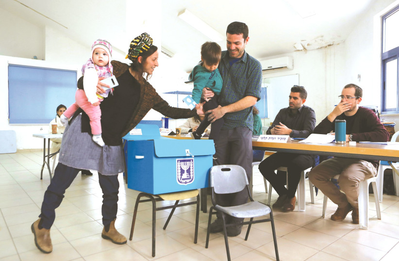 A FAMILY prepares to cast a ballot at a polling station in Nokdim last March. (photo credit: RONEN ZVULUN/REUTERS)
