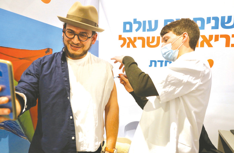 A MAN takes a picture of himself receiving a coronavirus vaccine at a Meuhedet Health Fund center in Jerusalem this week. (photo credit: MARC ISRAEL SELLEM/THE JERUSALEM POST)