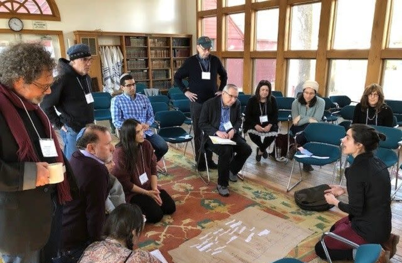 "Mati Esther Engel, bottom right, a performance artist, ritualist and spiritual care practitioner, speaks to participants at a gathering of Kenissa, a network of Jewish ""communities of meaning,"" held in March 2020 in Falls Village, Conn.  (photo credit: KENISSA)"