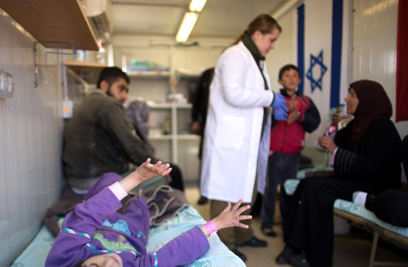 A member of the IDF medical team tends to Syrian women and children, who were injured in Syria's ongoing civil war, at a military hospital in the Golan Heights (photo credit: REUTERS/MENAHEM KAHANA/POOL)