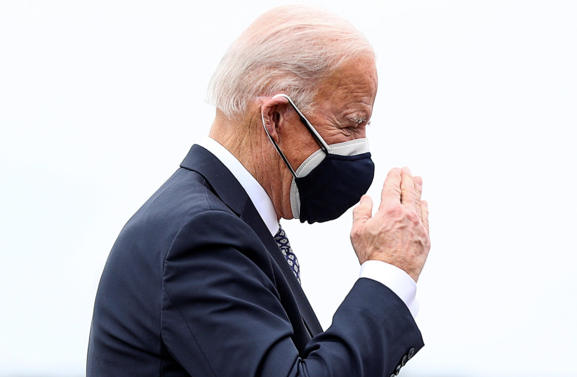 US President Joe Biden returns a salute while boarding Air Force One as he departs Washington for travel to Michigan at Joint Base Andrews, Maryland, US, February 19, 2021. (photo credit: TOM BRENNER/REUTERS)