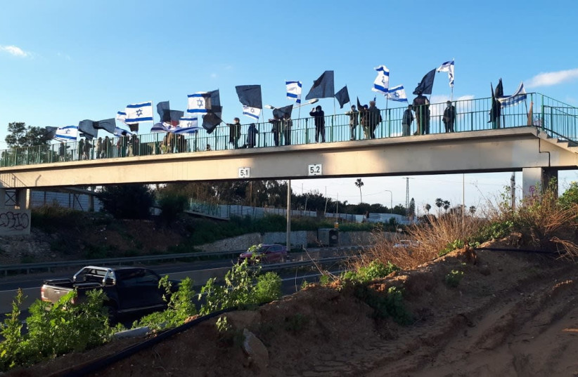 Protesters gather at the Neurim Bridge ahead of week 35 of the Balfour protests against Prime Minister Benjamin Netanyahu, Feb. 20, 2021. (photo credit: AVSHALOM SASSONI/MAARIV)