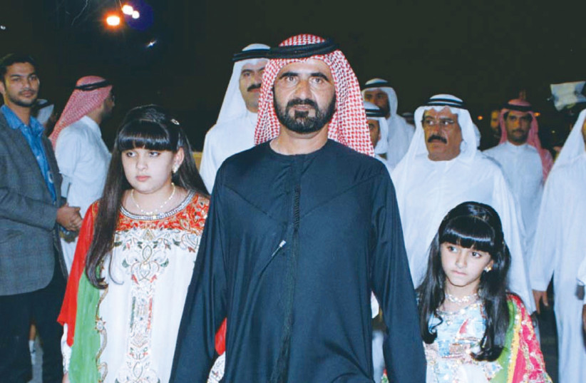 A 1999 PHOTO of Sheikh Mohammed Bin Rashid Al Maktoum, with his traditionally dressed daughters, Sheikha Latifa (left) and Sheikha Mariam.  (photo credit: REUTERS)
