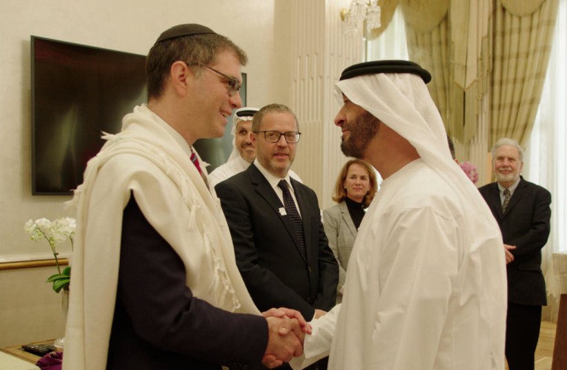 Chief Rabbi of the Jewish Council of the Emirates Rabbi Yehuda Sarna meets with Crown Prince of Abu Dhabi Sheikh Mohammed bin Zayed bin Sultan Al Nahyan at ceremony in 2019 in which the crown prince was given a Torah scroll dedicated to his father's memory.  (photo credit: RELIGION MEDIA COMPANY)