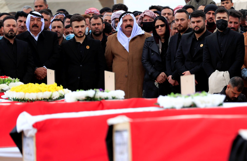 Mourners stand next to the coffins with the remains of people from the Yazidi minority, who were killed by Islamic State militants, after they were exhumed from a mass grave, to bury them in Kojo, Iraq February 6, 2021.  (photo credit: REUTERS/THAIER AL-SUDANI)