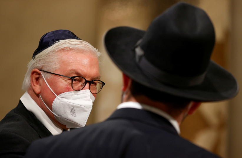 German President Frank-Walter Steinmeier speaks with a rabbi following a ceremony to complete the historic Sulzbach Torah Scroll from 1792, rediscovered in 2013 and just restored, on the 76th anniversary of the liberation of Nazi Germany's Auschwitz death camp, on International Holocaust Remembrance (photo credit: ODD ANDERSEN/POOL VIA REUTERS)