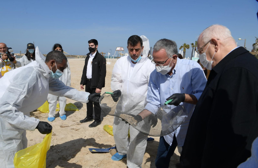President Reuven Rivlin visits cleanup efforts at Herziliya beach after oil spill (photo credit: AMOS BEN-GERSHOM/GPO)