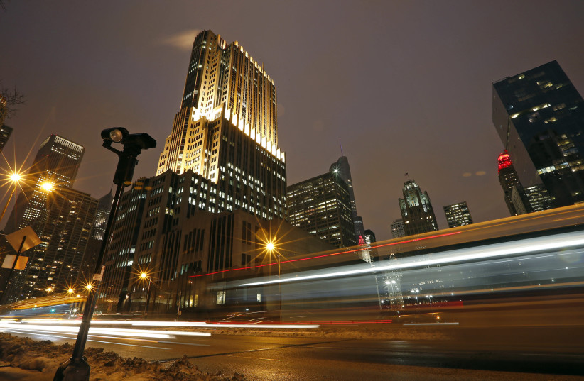 Cars cause streaks of lights as they drive past a red light camera in downtown Chicago (photo credit: JIM YOUNG / REUTERS)