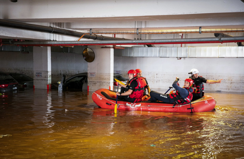 Israeli firefighters sit in a rescue boat as they search for people at a parking lot that was flooded following heavy rainfall in Ness Ziona, November 21, 2020. (photo credit: YOSSI ALONI/FLASH90)