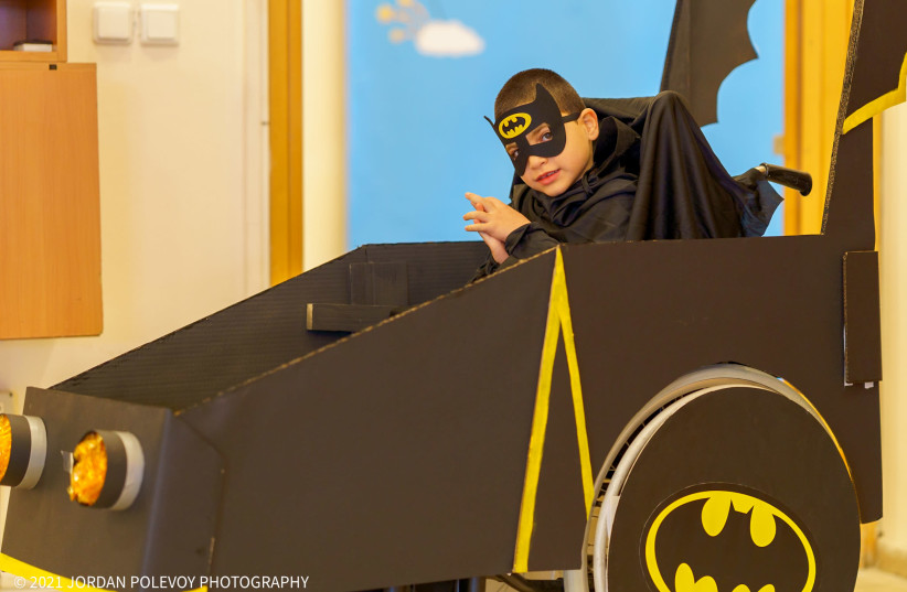 A disabled child is seen wearing a custom batman costume incorporating the wheelchair as a batmobile ahead of Purim. (photo credit: JORDAN POLEVOY)