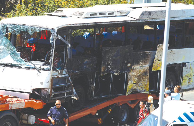 A truck carries the bus that was damaged in a bomb blast outside Burgas Airport, July 19, 2012. (photo credit: STOYAN NENOV/REUTERS)