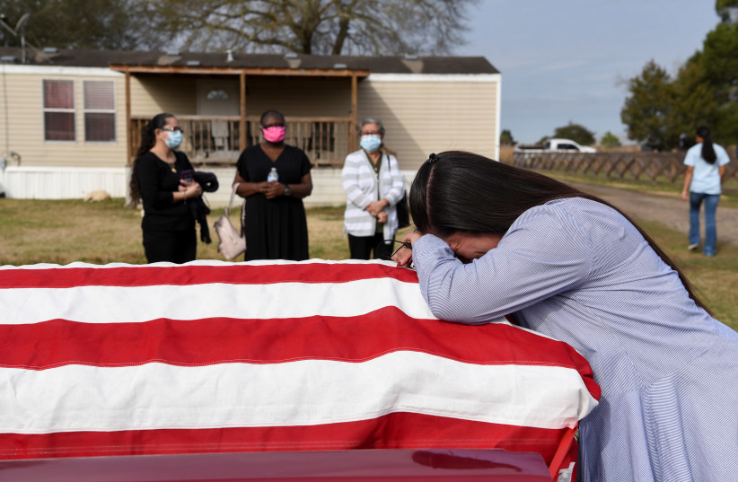 Lila Blanks reacts next to the casket of her husband, Gregory Blanks, 50, who died from complications from the coronavirus disease (COVID-19), ahead of his funeral in San Felipe, Texas, US, January 26, 2021. (photo credit: CALLAGHAN O'HARE/REUTERS)