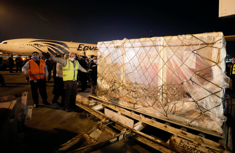 "Workers offload pallets containing coronavirus disease (COVID-19) vaccine ""Sinopharm"" doses as they arrive from China at Cairo International Airport amid the coronavirus disease (COVID-19) pandemic in Cairo, Egypt February 23, 2021 (photo credit: MOHAMED ABD EL GHANY/REUTERS)"
