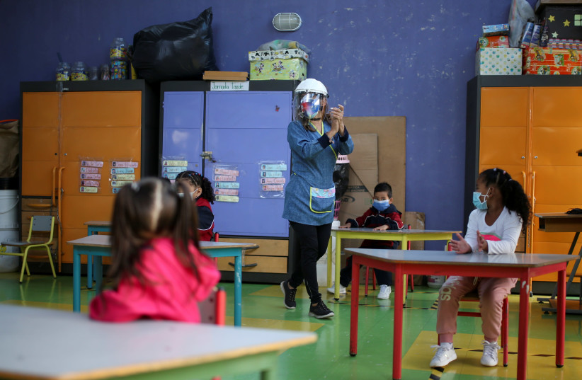 A teacher walks in a classroom with students keeping social distancing in a public school, after the reactivation of face-to-face classes, amidst an outbreak of the coronavirus disease (COVID-19), in Bogota, Colombia February 15, 2021 (photo credit: LUISA GONZALEZ/REUTERS)