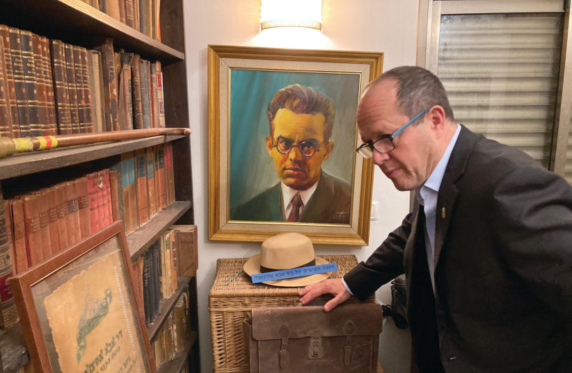 MK NIR BARKAT inspects a document at Beit Abba alongside a portrait of Abba Ahimeir. (photo credit: Courtesy)